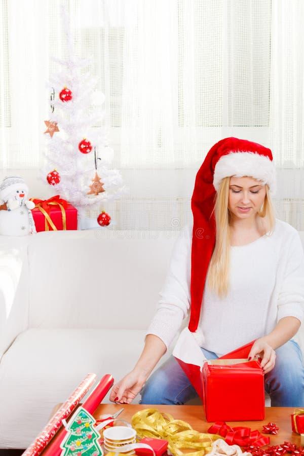 Jovem mulher que prepara presentes para o Natal fotos de stock royalty free