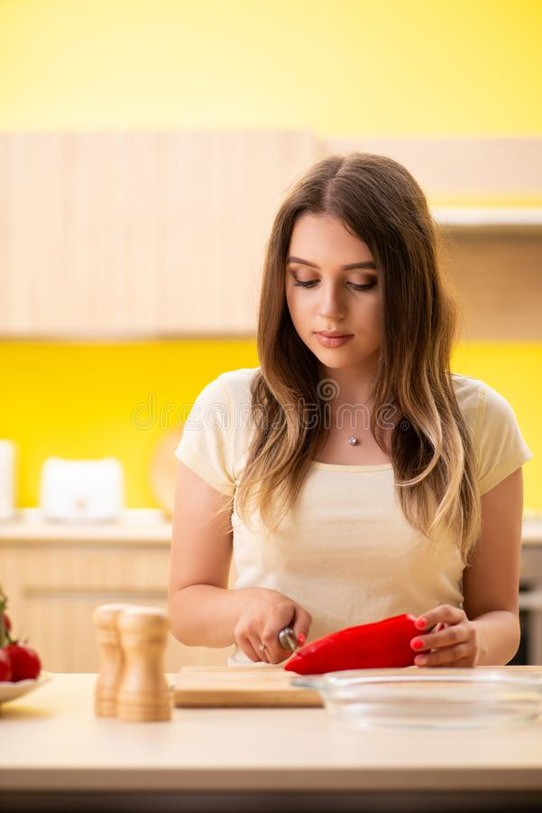 A jovem mulher que prepara a salada em casa na cozinha foto de stock royalty free