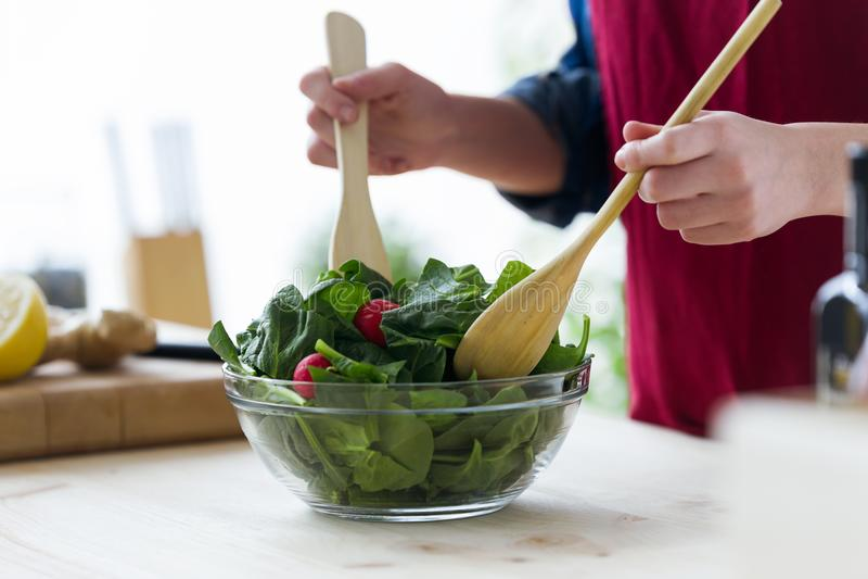 Jovem mulher que prepara a salada na cozinha em casa imagens de stock