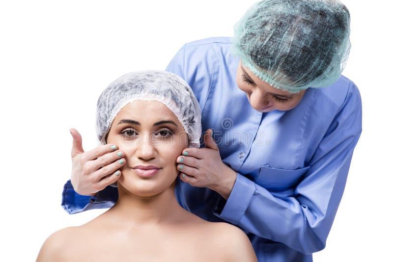 A jovem mulher que prepara-se para a cirurgia plástica isolada no branco imagens de stock
