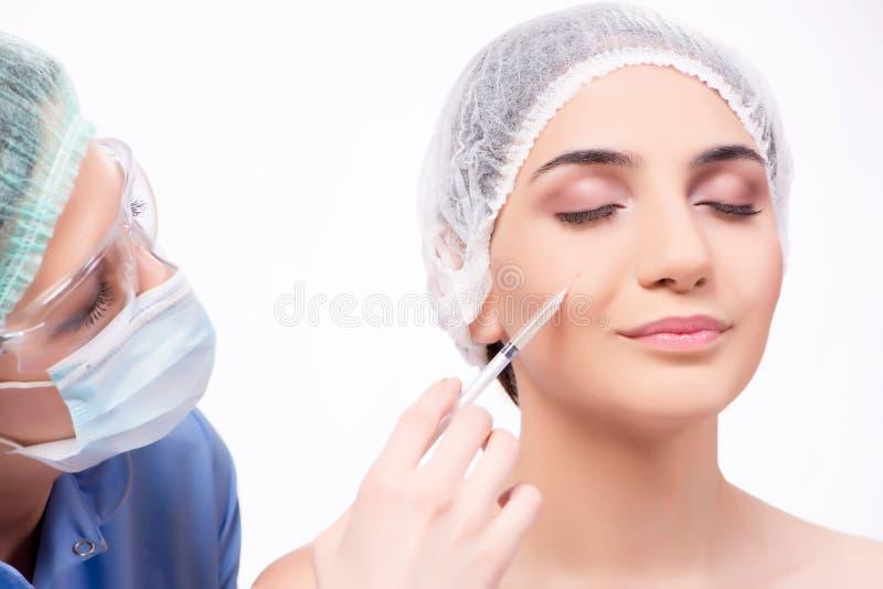 A jovem mulher que prepara-se para a cirurgia plástica isolada no branco imagem de stock royalty free
