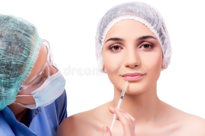 A jovem mulher que prepara-se para a cirurgia plástica isolada no branco fotografia de stock