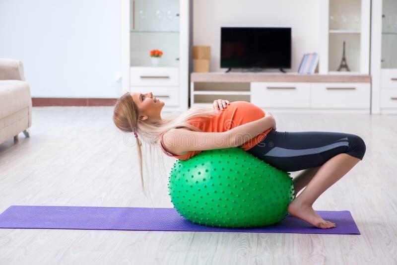 A jovem mulher que prepara-se para o nascimento que exercita em casa foto de stock royalty free