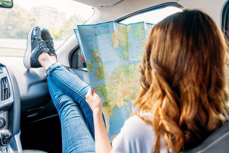 Jovem mulher que prepara-se para viajar pelo carro e que olha no mapa fotografia de stock