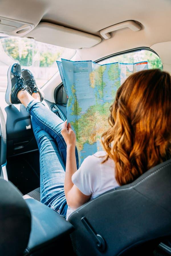 Jovem mulher que prepara-se para viajar pelo carro e que olha no mapa foto de stock royalty free
