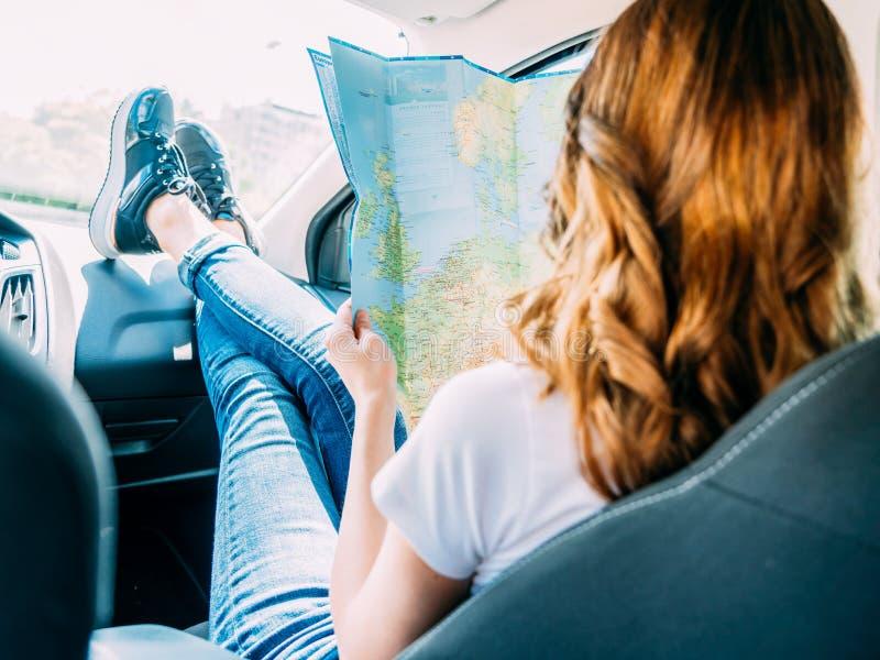 Jovem mulher que prepara-se para viajar pelo carro e que olha no mapa imagem de stock royalty free