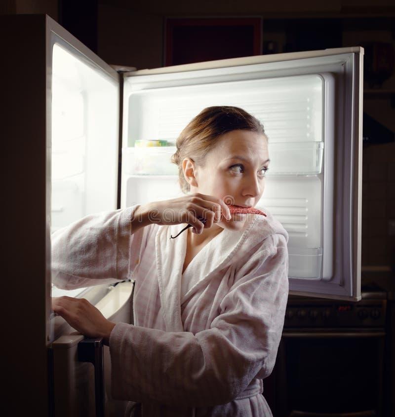 Jovem mulher que procura algum petisco no refrigerador tarde na noite imagem de stock