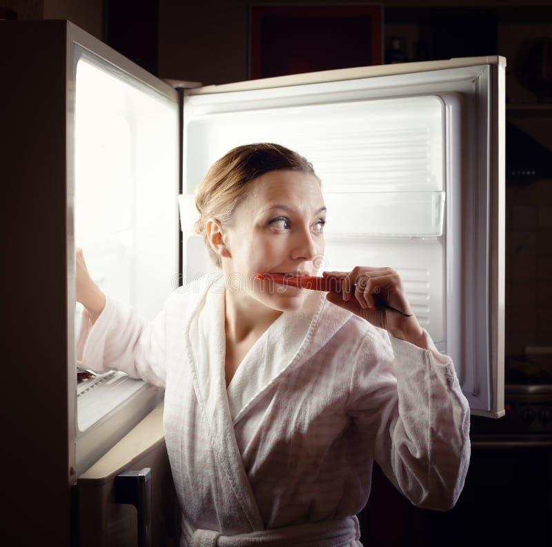 Jovem mulher que procura algum petisco no refrigerador tarde na noite fotos de stock royalty free