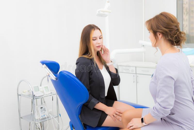 Jovem mulher que queixa-se ao dentista sobre a dor de dente imagens de stock