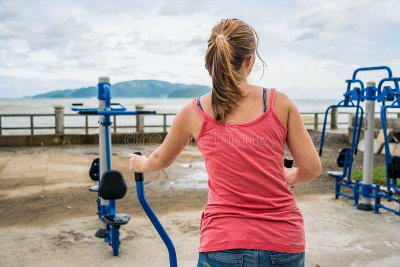 A jovem mulher que quer perder o peso é contratada no gym imagem de stock