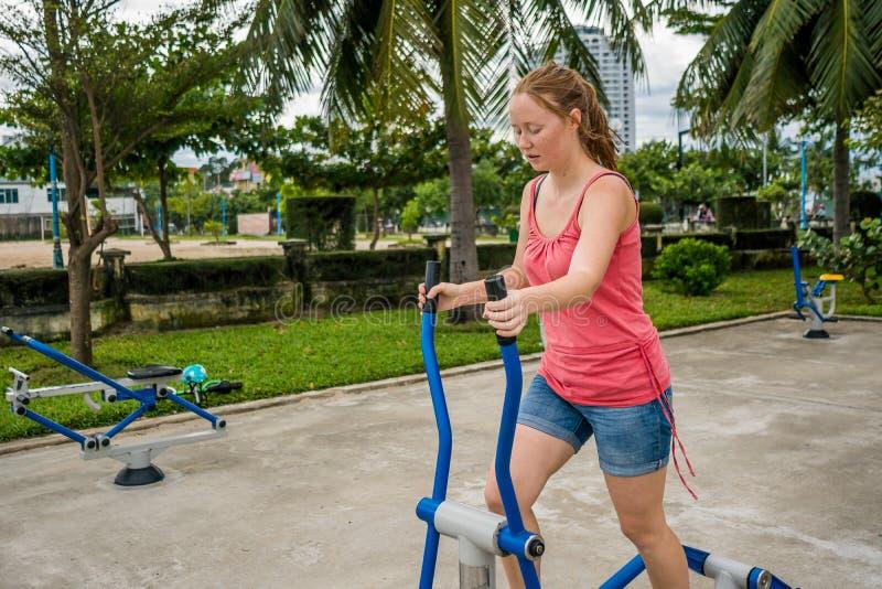 A jovem mulher que quer perder o peso é contratada no gym foto de stock royalty free
