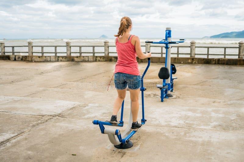 A jovem mulher que quer perder o peso é contratada no gym imagem de stock royalty free