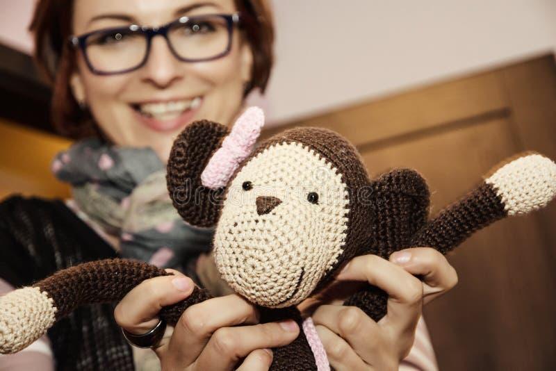 Jovem mulher que realiza na boneca feita malha mãos do macaco foto de stock royalty free