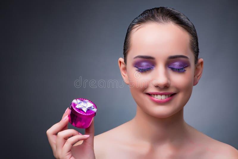 A jovem mulher que recebe o giftbox pequeno imagens de stock