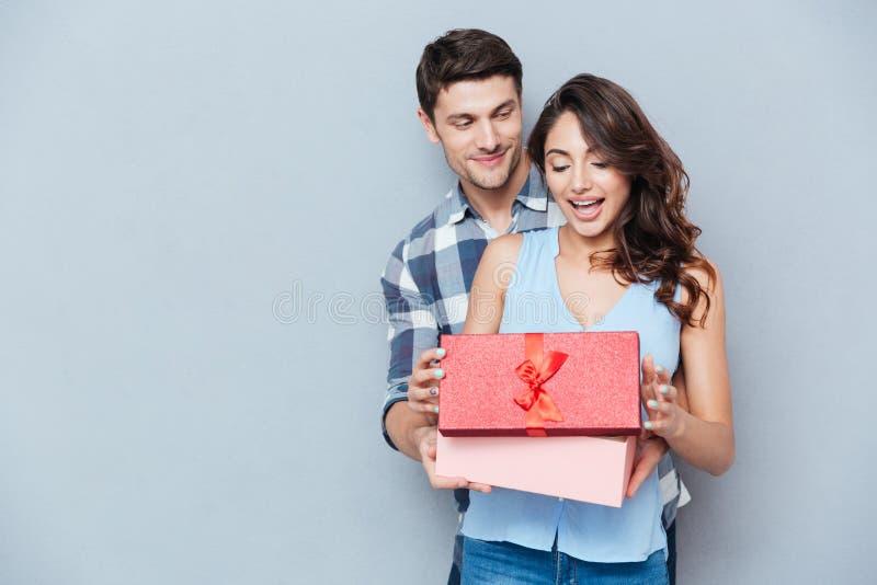 Jovem mulher que recebe o presente de seu noivo sobre o fundo cinzento foto de stock