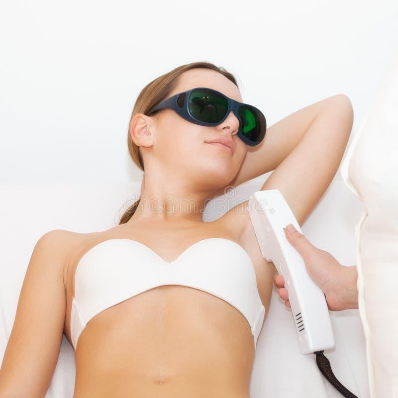 Jovem mulher que recebe o tratamento do laser do epilation imagens de stock