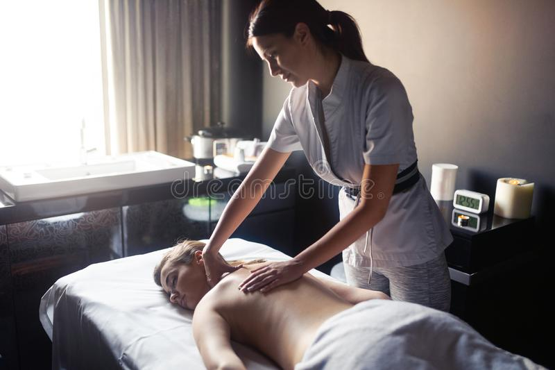 Jovem mulher que recebe uma massagem traseira em um centro dos termas imagem de stock royalty free