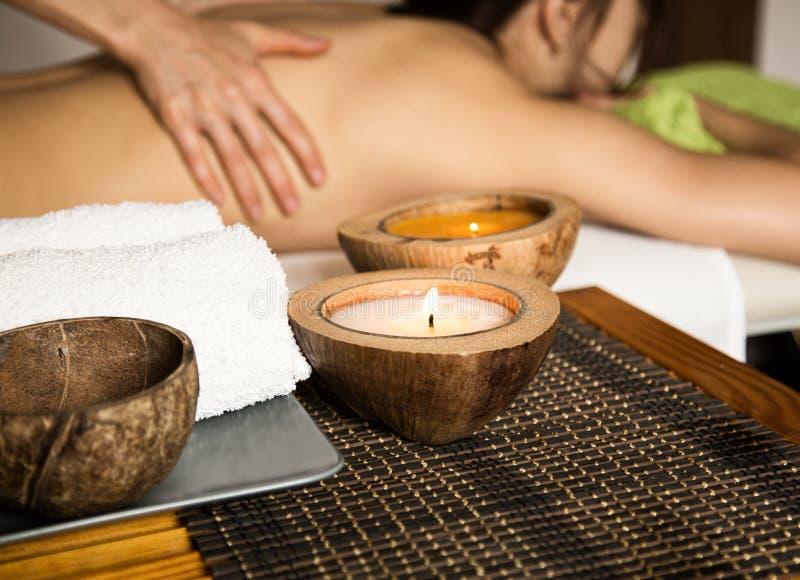 Jovem mulher que recebe uma massagem traseira no salão de beleza dos termas close-up de uma vela e de toalhas fotografia de stock
