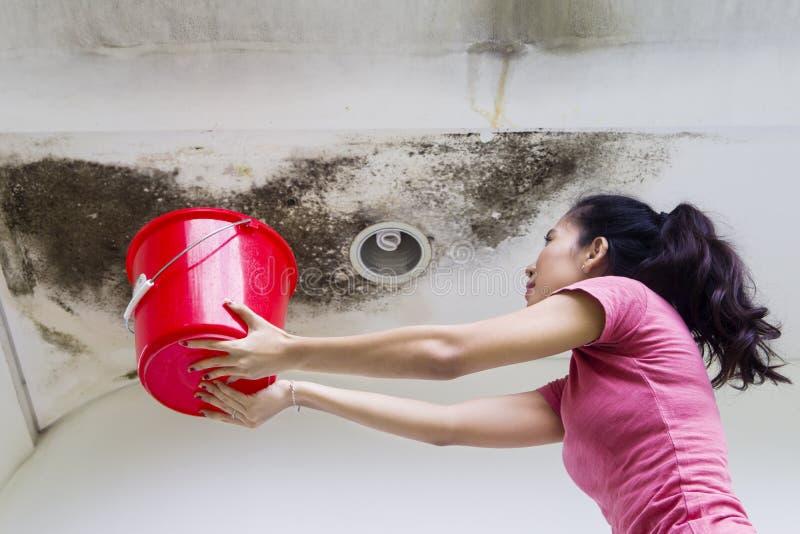 Jovem mulher que recolhe a água da chuva das gotas fotografia de stock royalty free
