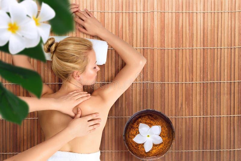 Jovem mulher que relaxa com massagem nos termas fotografia de stock