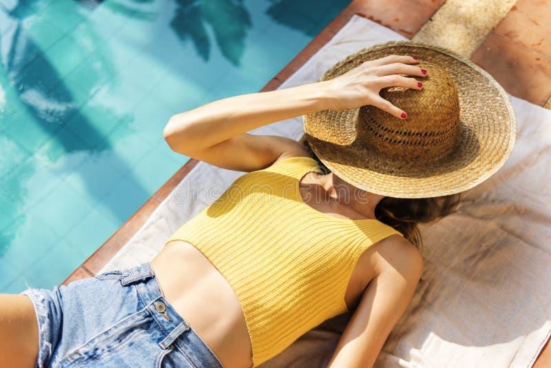 Jovem mulher que relaxa e que bronzea-se a piscina foto de stock royalty free