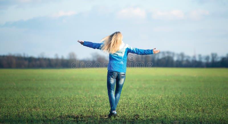 Jovem mulher que relaxa e que dança no prado lazer do divertimento imagens de stock royalty free