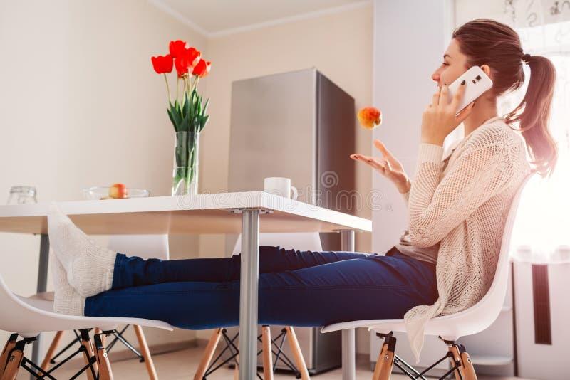 Jovem mulher que relaxa e que fala no telefone na cozinha Chá da menina e maçã bebendo dos lances acima Projeto moderno da cozinh fotografia de stock royalty free
