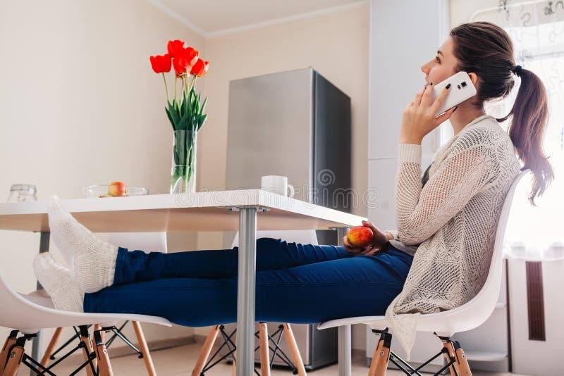 Jovem mulher que relaxa e que fala no telefone na cozinha Projeto moderno da cozinha imagem de stock