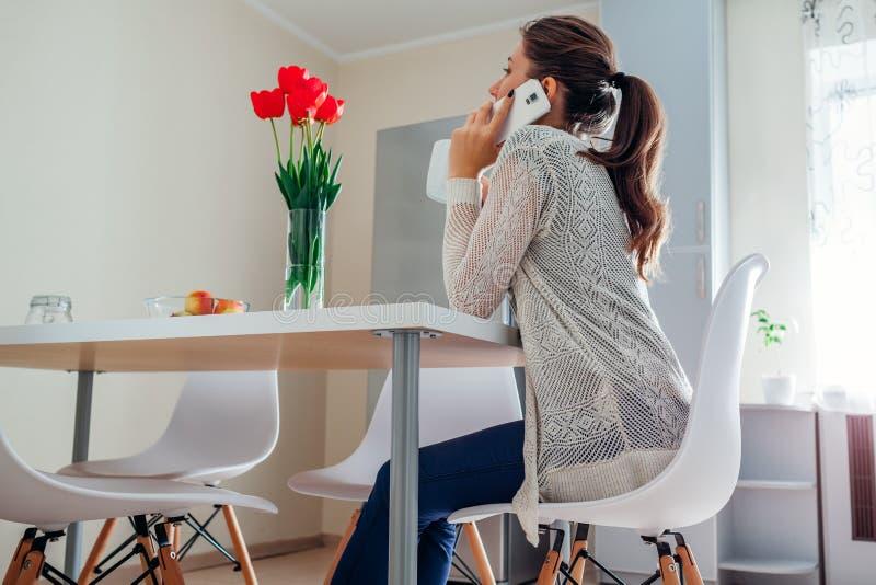 Jovem mulher que relaxa e que fala no telefone na cozinha Projeto moderno da cozinha imagens de stock