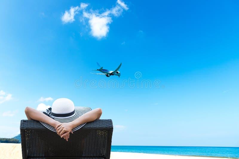 A jovem mulher que relaxa e vê o avião na praia bonita fotografia de stock royalty free