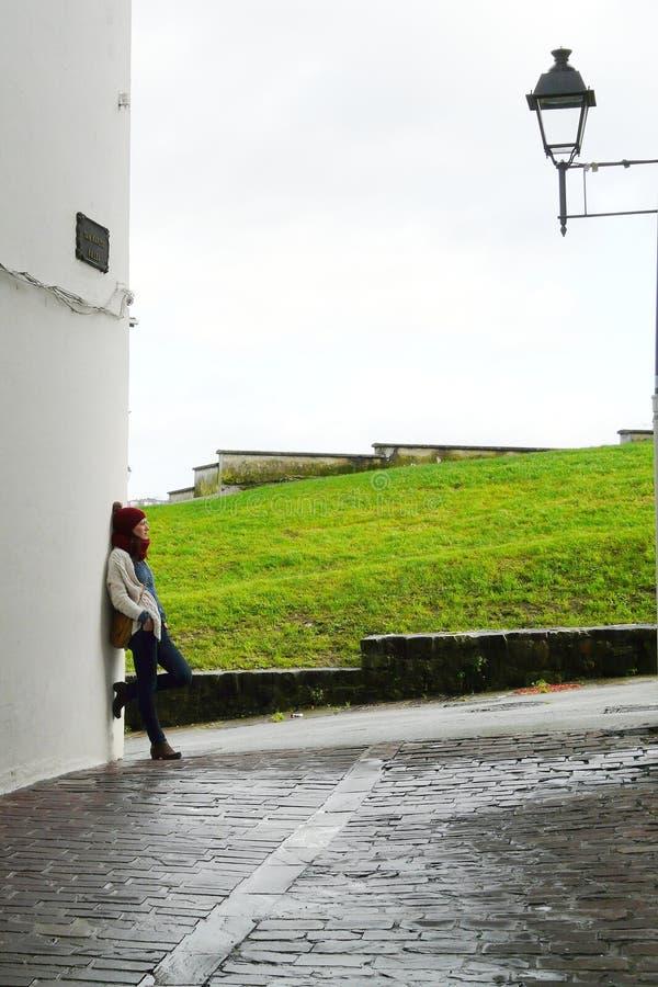 Jovem mulher que relaxa em ruas velhas da vila de Hondarribia durante uma caminhada da manhã do inverno, país Basque, Espanha foto de stock royalty free