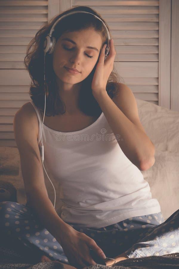 Jovem mulher que relaxa em sua cama, está escutando a música imagens de stock royalty free