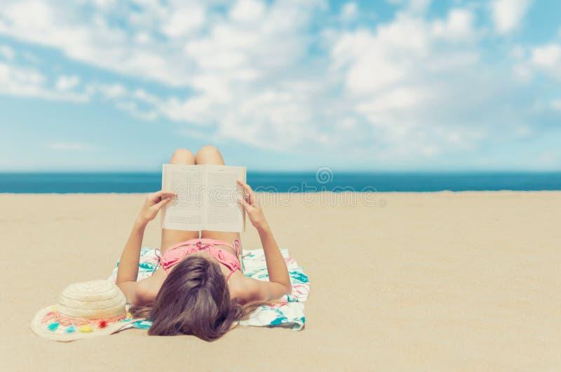 Jovem mulher que relaxa lendo um livro na praia foto de stock