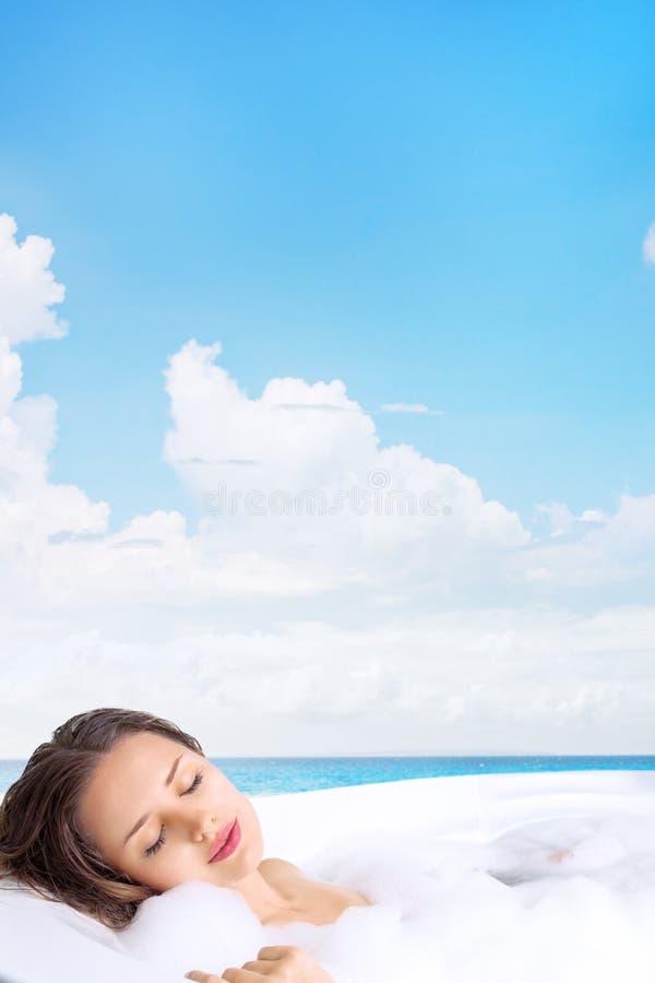 Jovem mulher que relaxa na banheira em termas tropicais fotos de stock