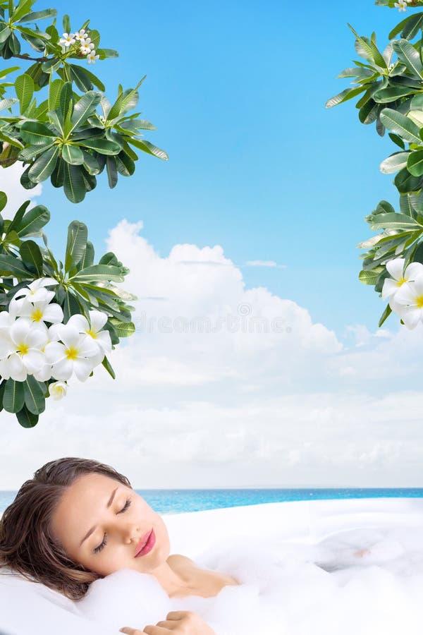 Jovem mulher que relaxa na banheira em termas tropicais imagens de stock royalty free