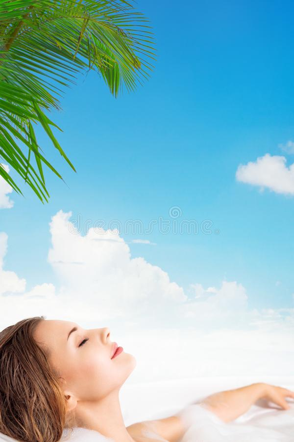 Jovem mulher que relaxa na banheira em termas tropicais fotografia de stock royalty free
