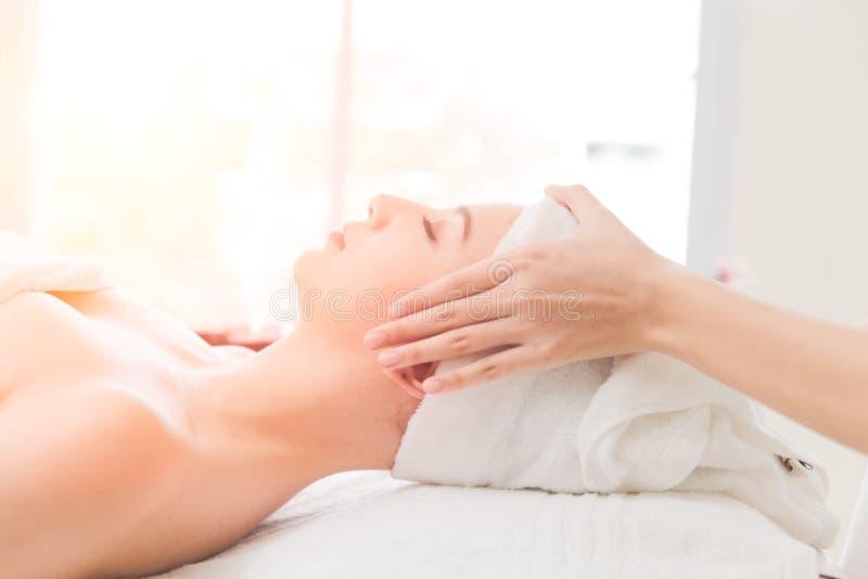 Jovem mulher que relaxa na massagem da cabeça dos termas da saúde fotos de stock royalty free