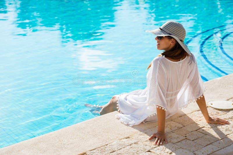 Jovem mulher que relaxa na piscina em férias de verão fotos de stock royalty free