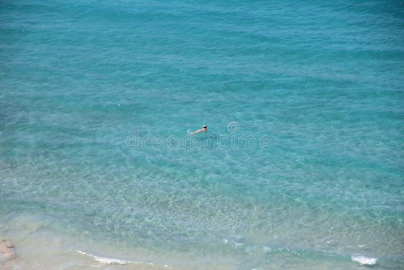 A jovem mulher que relaxa na superfície transparente azul do mar, aprecia as férias de verão, flutuando na água claro imagens de stock royalty free
