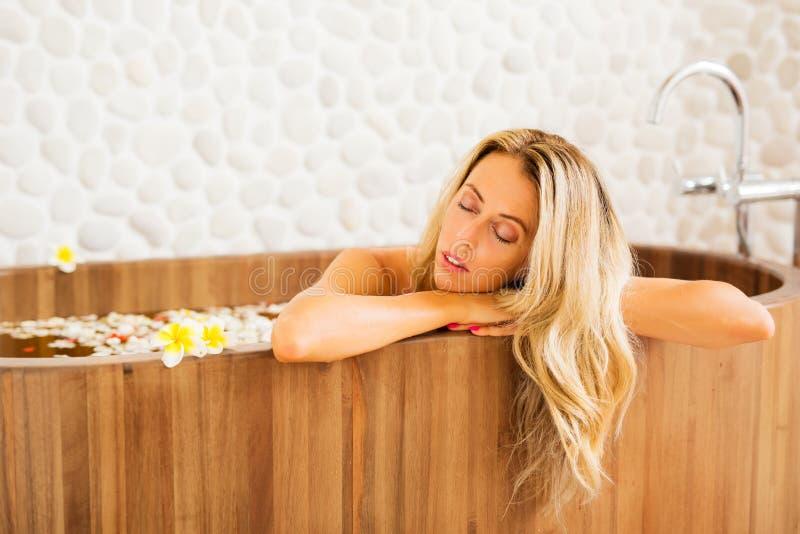 Jovem mulher que relaxa no banho de madeira fotos de stock royalty free