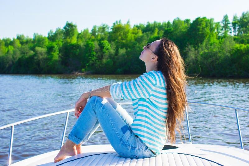 Jovem mulher que relaxa no iate no dia de verão foto de stock