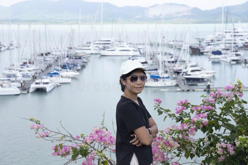 Jovem mulher que relaxa no monte perto do barco fotografia de stock