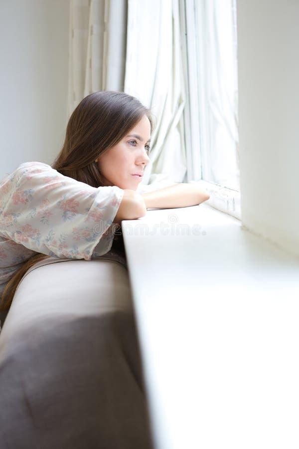 Jovem mulher que relaxa pela janela em casa fotos de stock