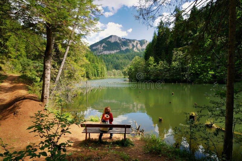 Jovem mulher que relaxa perto de um lago e que admira a paisagem fotografia de stock royalty free