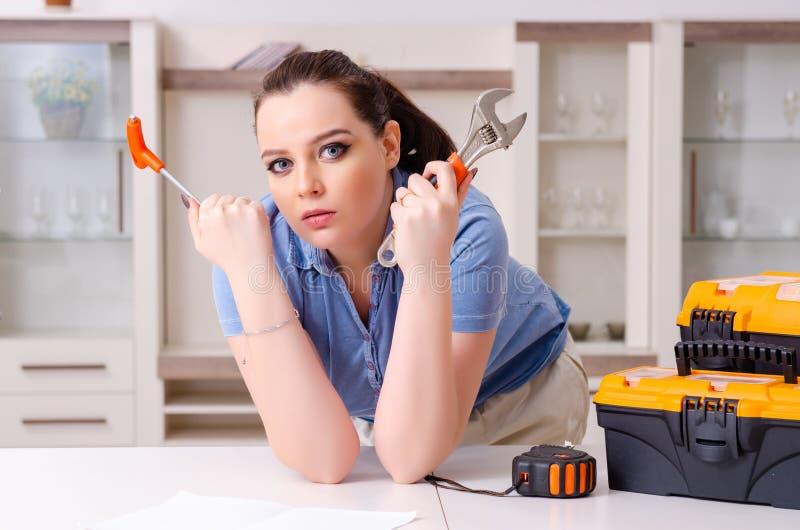 Jovem mulher que repara a cadeira em casa imagem de stock royalty free