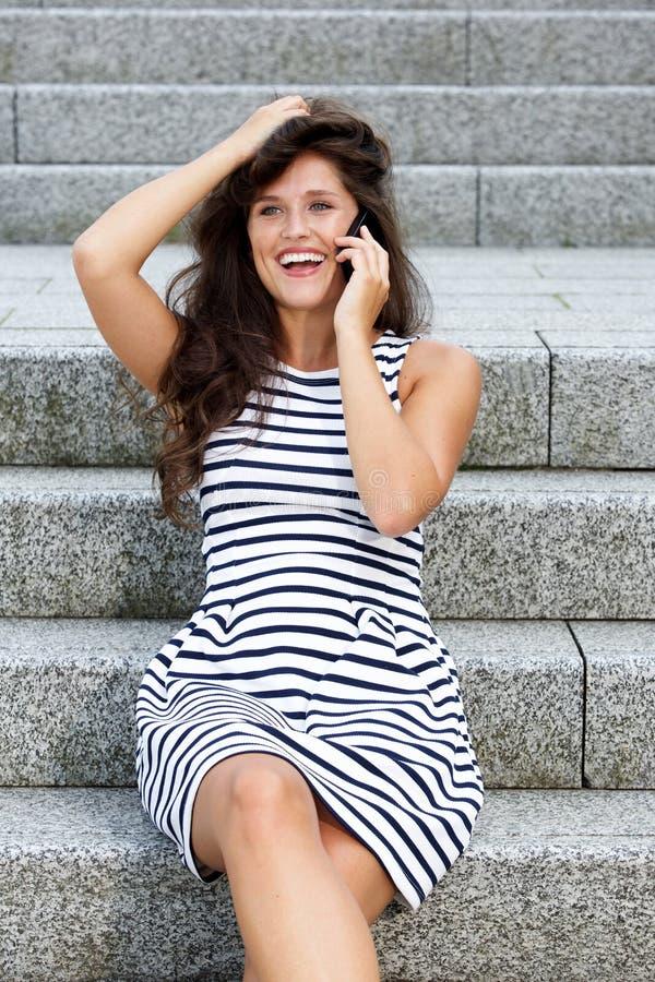 Jovem mulher que ri ao falar no telefone celular imagens de stock royalty free
