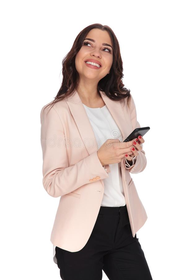 A jovem mulher que ri ao texting no telefone e olha acima foto de stock royalty free