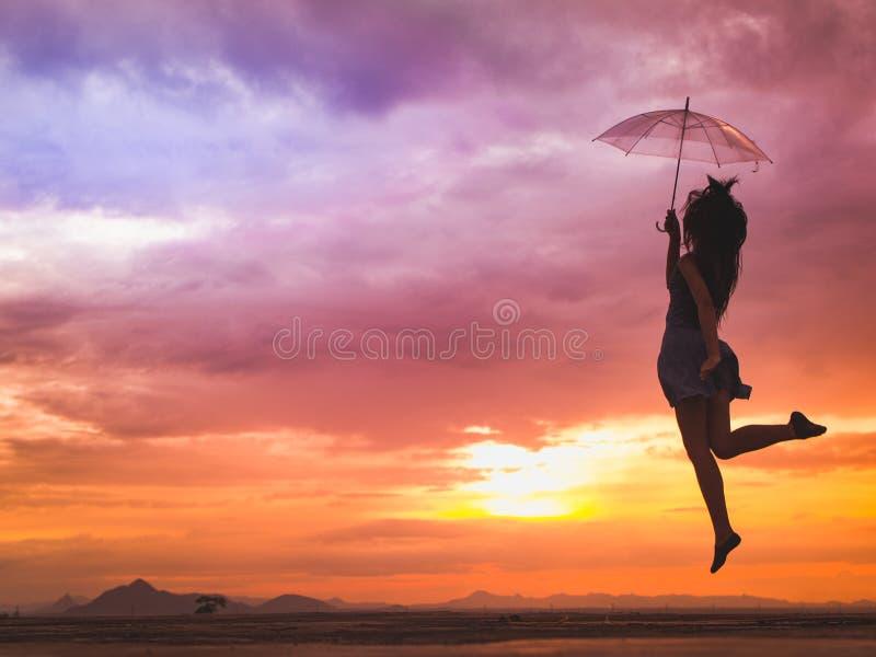 A jovem mulher que salta com o guarda-chuva no por do sol fotografia de stock royalty free