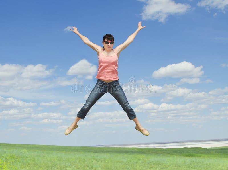 A jovem mulher que salta na grama verde sobre o céu azul fotografia de stock