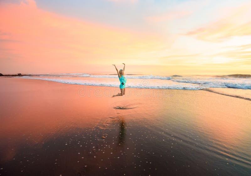 A jovem mulher que salta na praia em bali em Indonésia imagens de stock royalty free